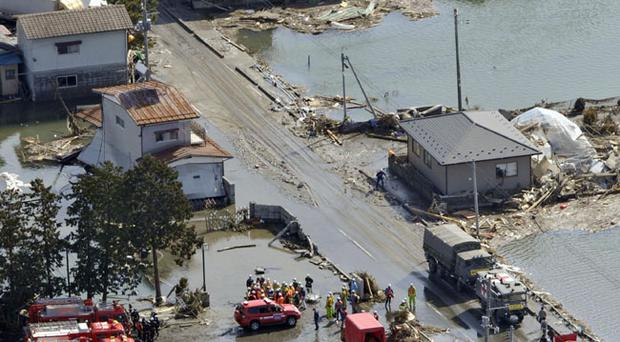 Firefighters and rescuers conduct their operations in Watari, Miyagi, northern Japan Monday, March 14, 2011 following Friday's massive earthquake and the ensuing tsunami. (AP Photo/Kyodo News) JAPAN OUT, MANDATORY CREDIT, NO SALES IN CHINA, HONG KONG, JAPAN, SOUTH KOREA AND FRANCE