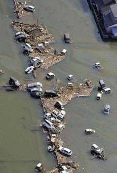 Vehicles are left on a flooded street in Watari, Miyagi, northern Japan Monday, March 14, 2011 following Friday's massive earthquake and the ensuing tsunami. (AP Photo/Kyodo News) JAPAN OUT, MANDATORY CREDIT, NO SALES IN CHINA, HONG KONG, JAPAN, SOUTH KOREA AND FRANCE