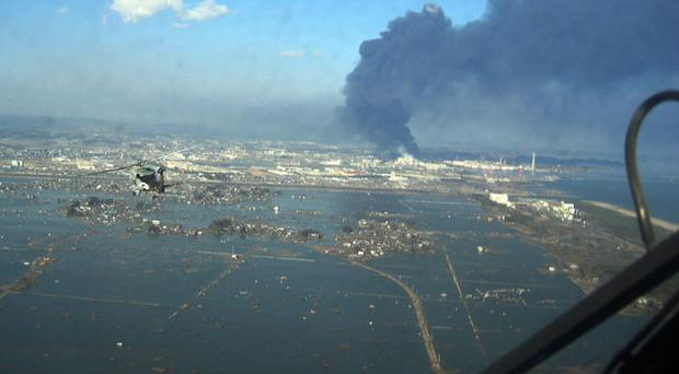 In this March 12, 2011 photo provided by the U.S. Navy, an SH-60B helicopter assigned to the Chargers of Helicopter Antisubmarine Squadron (HS) 14 from Naval Air Facility Atsugi flies over the city of Sendai, Japan to deliver more than 1,500 pounds of food to survivors of an 8.9 magnitude earthquake and a tsunami. The citizens of Ebina City, Japan, donated the food, and HS-14 is supporting earthquake and tsunami relief operations in Japan as directed. (AP Photo/U.S. Navy)