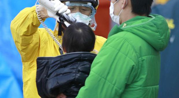 A child evacuated from areas surrounding the Fukushima nuclear facilities is checked for radiation exposure (AP)