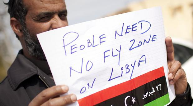 A Libyan man holds a sign calling for a no-fly zone near the border town of Musa'id (AP)
