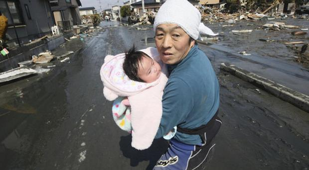 Upon hearing another tsunami warning, a father tries to flee for safety with his just reunited four-month-old baby girl who was spotted by Japan's Self-Defense Force member in the rubble of tsunami-torn Ishinomaki Monday, March 14, 2011, three days after a powerful earthquake-triggered tsunami hit northeast Japan.