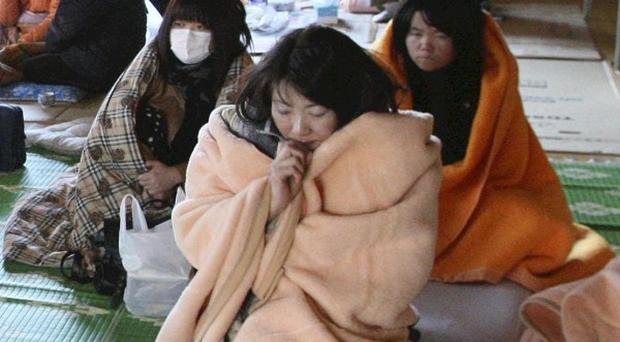 Women wrap themselves in blankets at an evacuation centre in Yamadamachi after Japan's earthquake and tsunami (AP)