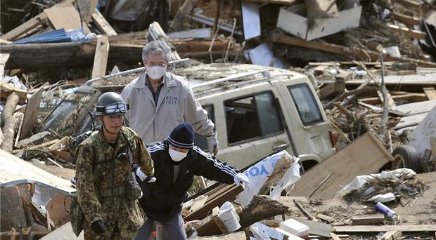 A soldier leads evacuees to safety in Noda, Iwate Prefecture, northern Japan (AP Photo/Kyodo News)