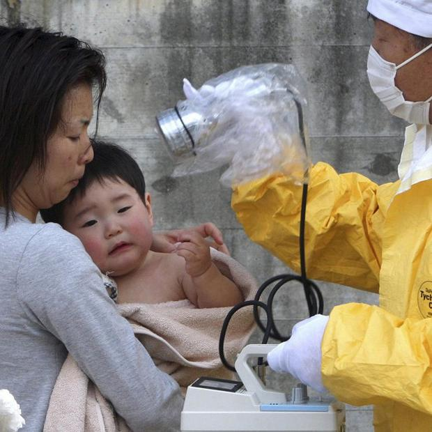 A one-year-old boy is re-checked for radiation exposure after being decontaminated in Nihonmatsu, Fukushima (AP)