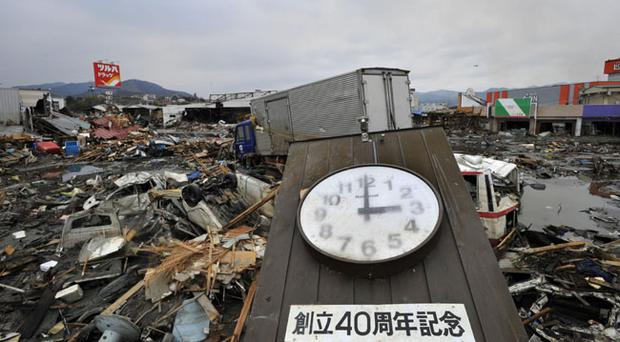 A clock that appears to indicate the time when a tsunami struck lies among the rubble in the city of Kesennuma, northeastern Japan, on Tuesday March 15, 2011. The Japanese characters read: