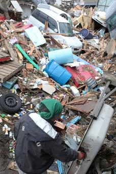 A local resident clears up in the area damaged by tsunami after a 9.0 magnitude strong earthquake struck on March 11 off the coast of north-eastern Japan, on March 15, 2011 in Sendai, Japan. The quake struck offshore at 2:46pm local time, triggering a tsunami wave of up to 10 metres which engulfed large parts of north-eastern Japan. The death toll continues to rise with fears that the official death count could well reach up to 10,000 in