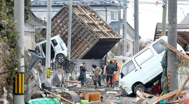 Local residents walk through an area damaged by tsunami after a 9.0 magnitude strong earthquake struck on March 11 off the coast of north-eastern Japan, on March 15, 2011 in Sendai, Japan. The quake struck offshore at 2:46pm local time, triggering a tsunami wave of up to 10 metres which engulfed large parts of north-eastern Japan. The death toll continues to rise with fears that the official death count could well reach up to 10,000 in