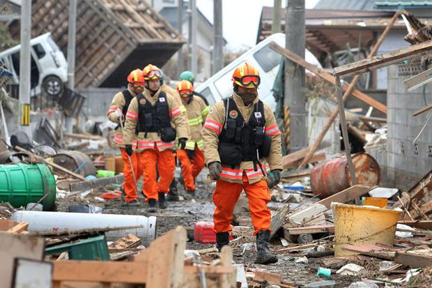 "Members of a Korean rescue team walk through an area damaged by earthquake and tsunami after a 9.0 magnitude strong earthquake struck on March 11 off the coast of north-eastern Japan, on March 15, 2011 in Sendai, Japan. The quake struck offshore at 2:46pm local time, triggering a tsunami wave of up to 10 metres which engulfed large parts of north-eastern Japan. The death toll continues to rise with fears that the official death count could well reach up to 10,000 in ""the most tragic event in Japanese history since World War Two""."
