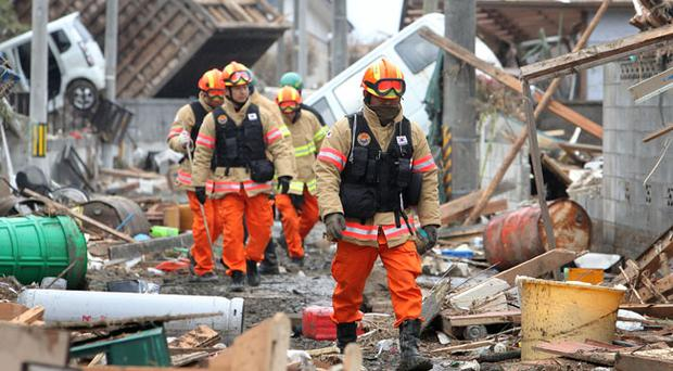 Members of a Korean rescue team walk through an area damaged by earthquake and tsunami after a 9.0 magnitude strong earthquake struck on March 11 off the coast of north-eastern Japan, on March 15, 2011 in Sendai, Japan. The quake struck offshore at 2:46pm local time, triggering a tsunami wave of up to 10 metres which engulfed large parts of north-eastern Japan. The death toll continues to rise with fears that the official death count could well reach up to 10,000 in