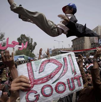 Anti-government protestors throw a boy into the air during a protest calling for the resignation of Yemeni President Ali Abdullah Saleh (AP)