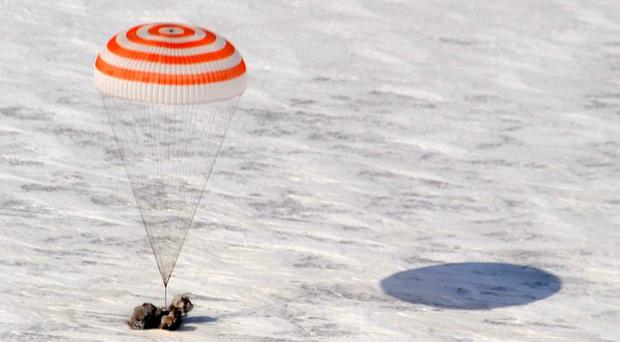A capsule carrying Russian cosmonauts Oleg Skripochka, Alexander Kaleri and US astronaut Scott Kelly lands in Kazakhstan (AP)