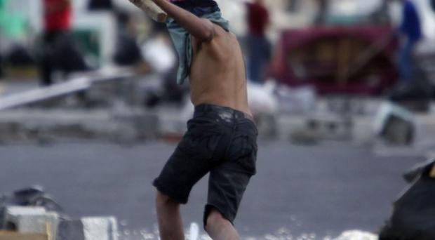 A Bahraini youth holds a piece of wood in the streets of Malkiya, Bahrain (AP)