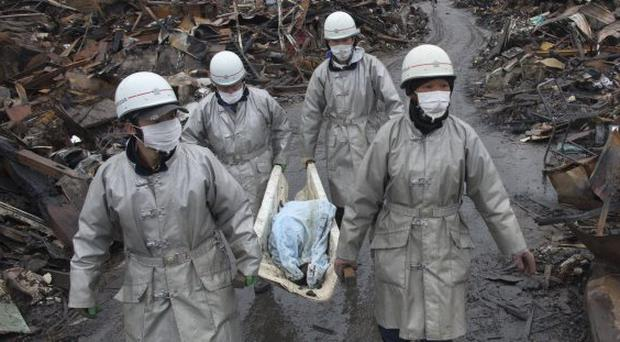 Rescue workers carry a charred body from the rubble of a village destroyed by the devastating earthquake, fires and tsunami