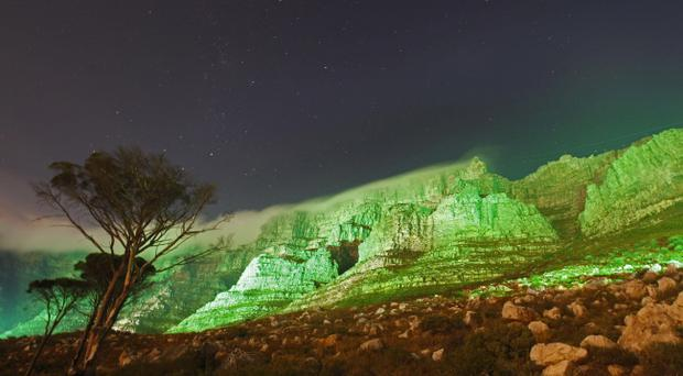 Table mountain is seen lit up in green, in a spectacular display to commemorate St Patrick's Day in Cape Town, South Africa, Thursday, March 17, 2011