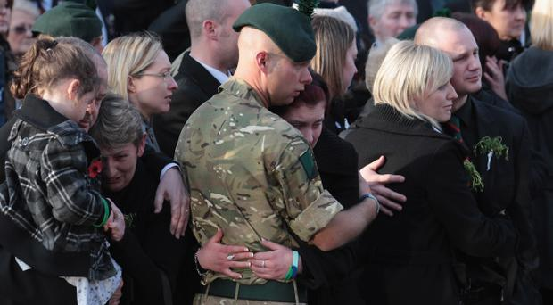 WOOTTON BASSETT, ENGLAND - MARCH 17: Mourners react as the hearse carrying the body of Lance Corporal Stephen McKee, passes along the High Street on March 17, 2011 in Wootton Bassett, England. Lance Corporal Stephen McKee, 27, was killed in an explosion in Afghanistan and his younger brother Michael, also serving with 1st Battalion, was one of the first on the scene. The soldier from Northern Ireland who was repatriated to nearby RAF Lyneham on St Patrick's Day was the first after it was announced yesterday that the town will be renamed Royal Wootton Bassett in recognition of its contribution to showing respect for fallen soldiers. (Photo by Matt Cardy/Getty Images)