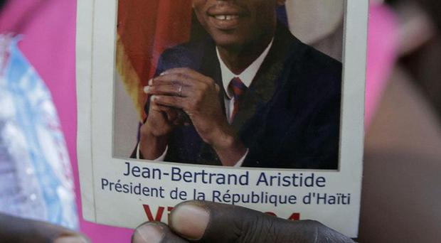 A woman holds a photo of Haiti's ousted President Jean-Bertrand Aristide during in Port-au-Prince (AP Photo/Dieu Nalio Chery)