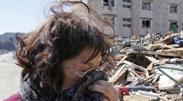 A woman cries for her missing husband in the area around her damaged apartment building in Onagawa, northeastern Japan (AP)