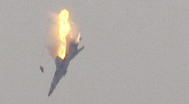 A warplane is seen being shot down over the outskirts of Benghazi, eastern Libya, Saturday, March 19 ... the image shows the pilot has ejected from the plane, 2011.
