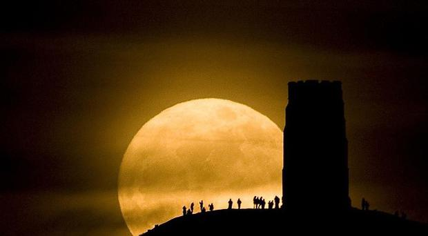 Revellers stand beside St Michael's Tower on Glastonbury Tor watching the Moon