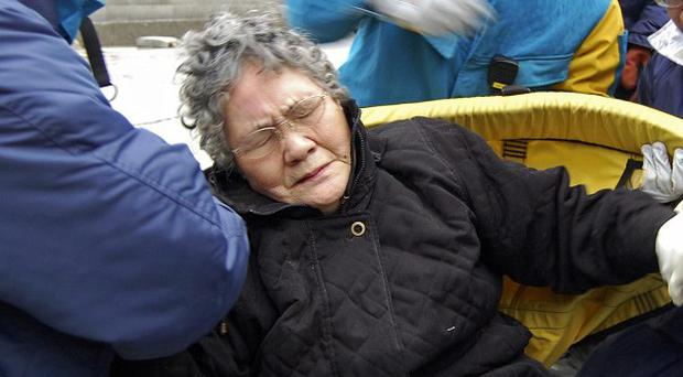 Sumi Abe, 80, is rescued from her destroyed home in Ishinomaki, Japan (AP)