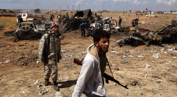 Libyan rebels walk past wrecked military vehicles belonging to Moammer Khaddafi forces bombed by the French airforce in al-Wayfiyah west of Benghazi