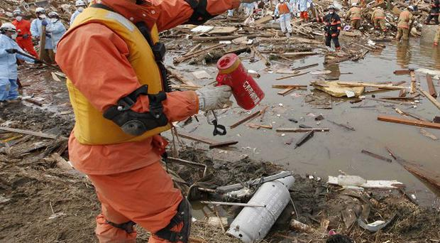 Rescuers sift through the remains of a property in the suburb of Natori, Japan (AP)