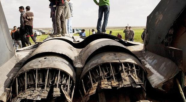 Libyans inspect the wreckage of a US F-15 fighter jet after it crashed east of Benghazi (AP)