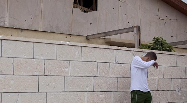 An Israeli youth stands next to a house damaged by a rocket fired by Palestinian militants from the Gaza Strip (AP)