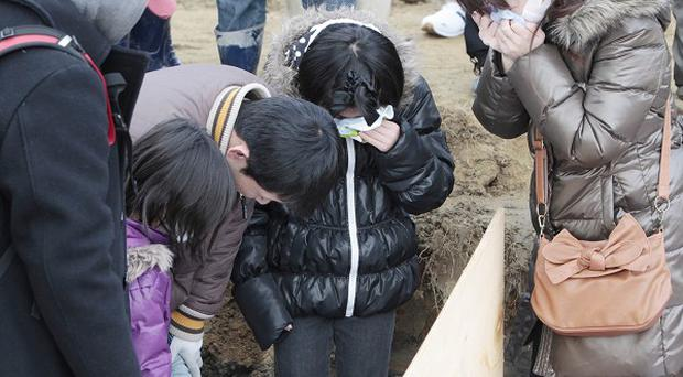 Relatives attend a burial ceremony for a victim of the tsunami in Higashimatsushima City, Miyagi Prefecture (AP)