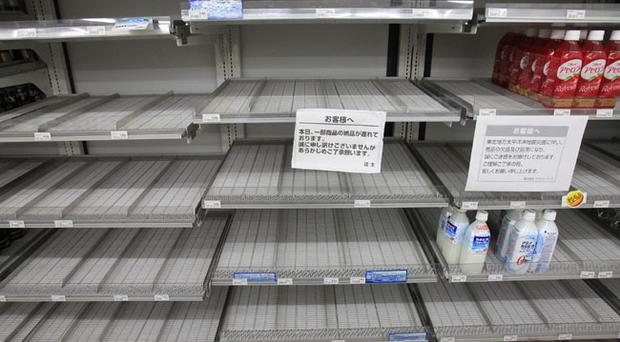 Shelves selling bottled water are empty at a convenience store in Tokyo Wednesday, March 23, 2011. A spike in radiation levels in Tokyo tap water spurred new fears about food safety Wednesday as rising black smoke forced another evacuation of workers trying to stabilize Japan's radiation-leaking nuclear plant. (AP Photo/Lee Jin-man)