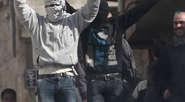 Anti-Syrian government protesters flash V-victory signs as they demonstrate in the southern city of Daraa, Syria (AP)