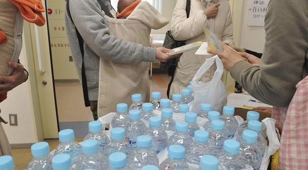 Mothers receive bottled water at a healthcare centre in Tokyo amid a shortage in shops and fears over tap water safety (AP)