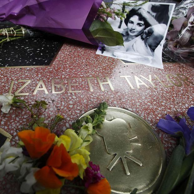 Flowers and a portrait adorn Elizabeth Taylor's star on the Hollywood Walk of Fame in Los Angeles