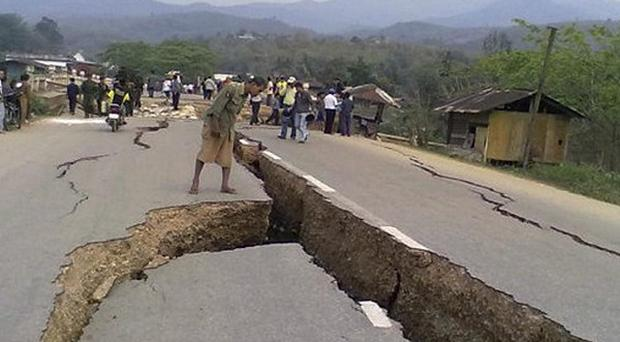 A resident looks into a huge crack in a road caused by an earthquake in Tarlay, Shan, Burma (AP)