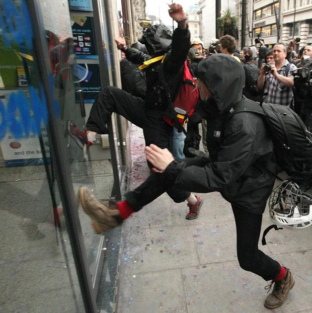 Protesters kick the doors of a branch of Santander on Piccadilly