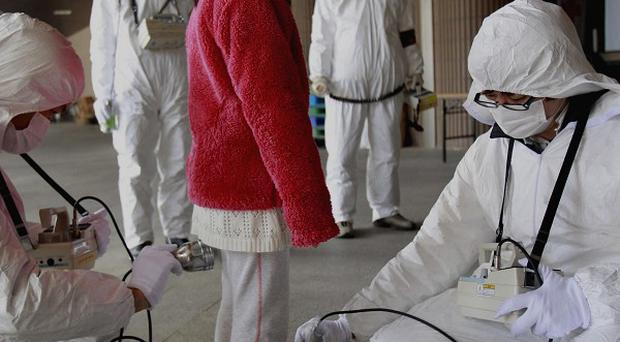 A young evacuee is screened at a shelter for leaked radiation from the damaged Fukushima nuclear plant in Japan (AP)