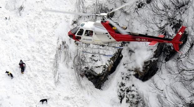 Rescue workers search for avalanche survivors near Bourg-St-Pierre, southern Switzerland (AP)
