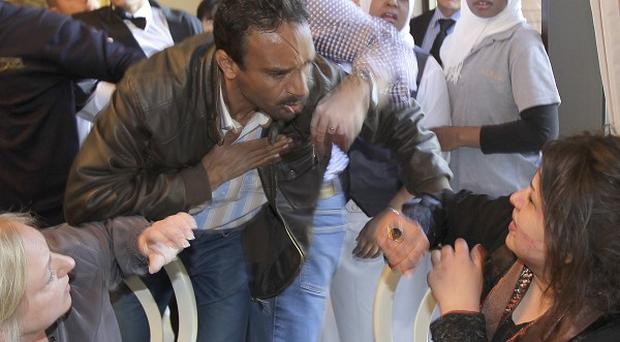 FT journalist Charles Clover attempts to stop a Libya ministry of information official from grabbing Iman Al-Obeidi (AP)