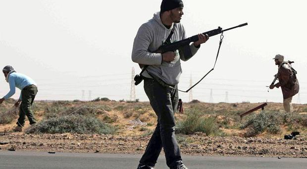 Libyan rebels are seen after being ambushed by forces loyal to Muammar Gaddafi 75 miles east of Sirte (AP)