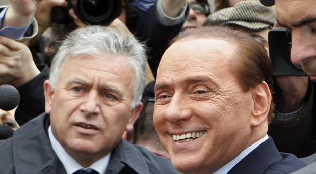 Silvio Berlusconi smiles for the cameras as he leaves the tribunal in Milan (AP)