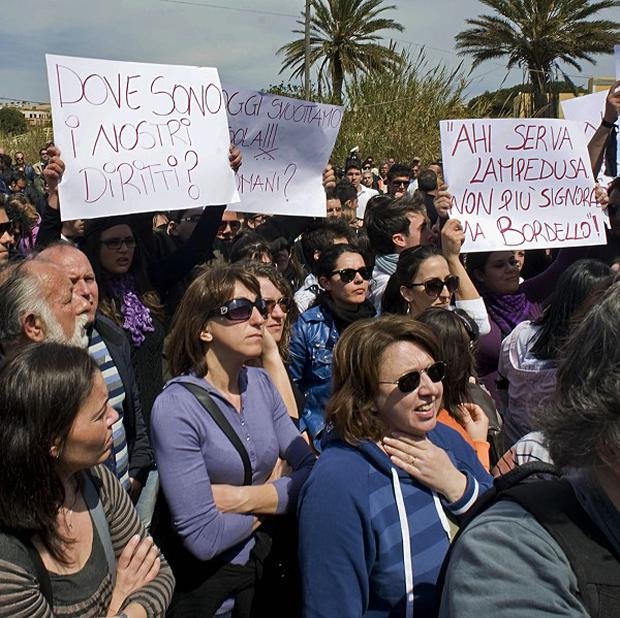 Lampedusa residents protest during Silvio Berlusconi's visit to the island (AP)