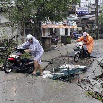Tourists make their way on a damaged road on Koh Samui island after heavy storms and rain (AP)