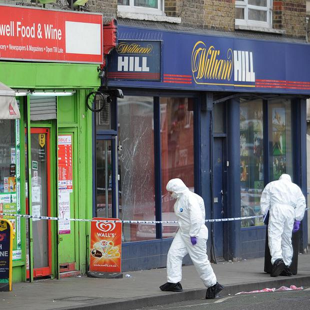 Forensic officers examine the scene in Brixton, where a five-year-old girl was shot (PA)