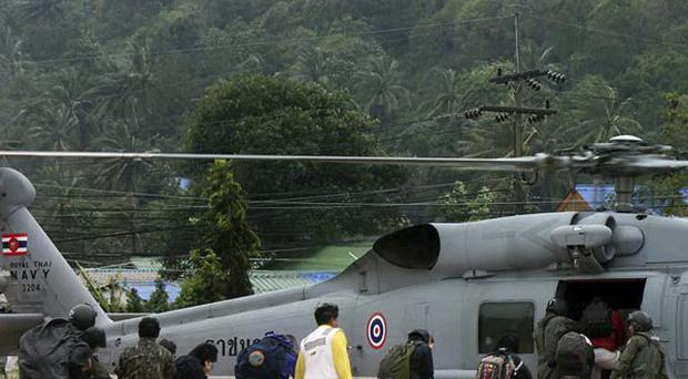 Thai navy officers evacuate tourists stranded on Koh Tao island by helicopter following heavy storms (AP)