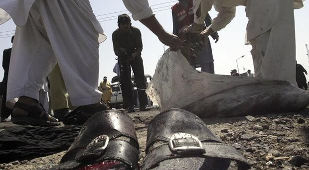Officials collect evidence at the site of a suicide bombing in north-west Pakistan (AP)