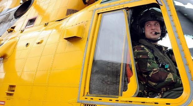 Prince William at the controls of a Sea King helicopter during a training exercise at Holyhead Mountain, having flown from RAF Valley in Anglesey