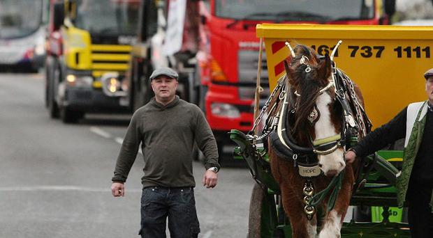 Hope the Shire horse, led by Wynne Hull and owner of Salford Skip Hire Tony Cauchi (left) at the head of a go-slow protest in Manchester