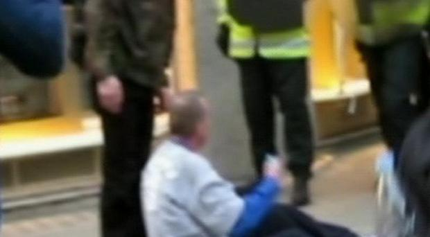 A still from video footage of newspaper seller Ian Tomlinson after he had been pushed to the ground