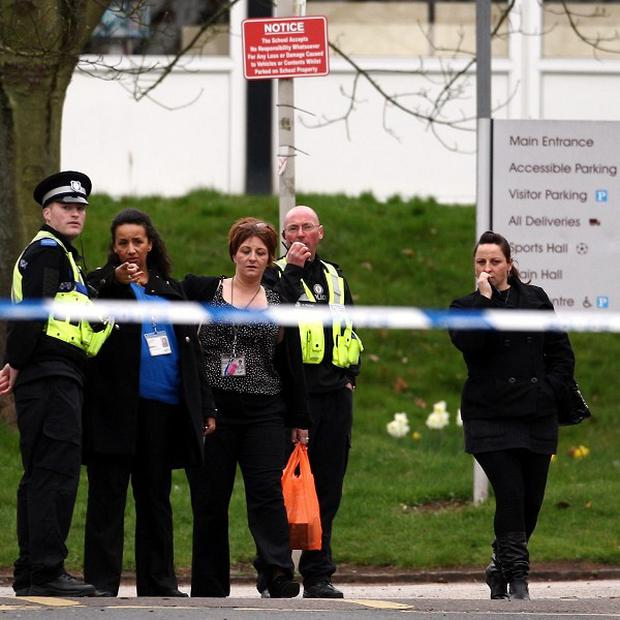 Police talk to members of the public outside Ridgewood High School after a teenage girl suffered stab wounds